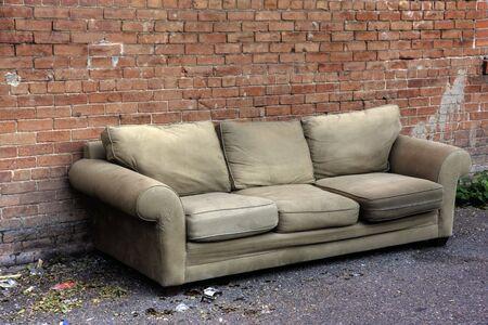 oude sofa weggegooid in een steegje, omgeven door trash en gebroken glas, tegen de rode bakstenen muur