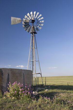 pawnee grassland: windmill, water pump and concrete tank in shortgrass prairie in Colorado Wyoming border area - Pawnee National Grassland