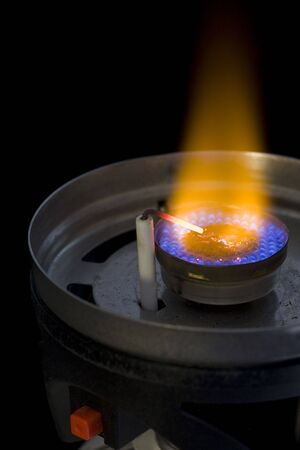 butane: flame burner of camping or backpacking stove with a piezoelectric igniter against black background Stock Photo