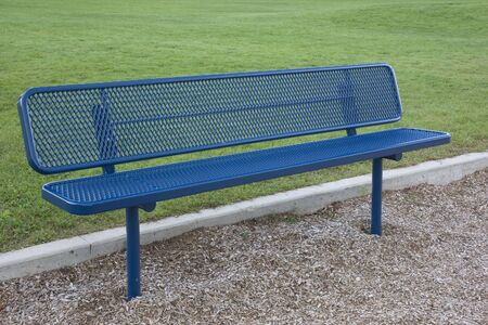 blue metal bench against green grass in a park or playground Stock Photo - 3511373