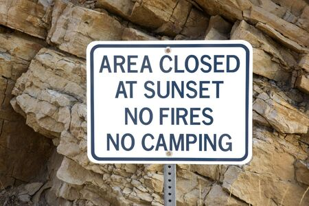 no fires: area closed at sunset, no fires or camping - whte warning sign in front of climbing rock cliff