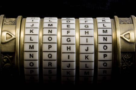 login word set up as a password to combination puzzle box (cryptex) with rings of letters; black background Stock Photo