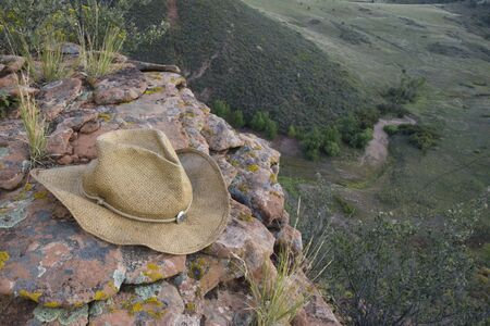 Straw cowboy hat on sandstone rocks with lichen at the edge of high cliff, a view of a valley below in shadow. Lory State Park near Fort Collins, Colorado. Stock Photo - 3583406