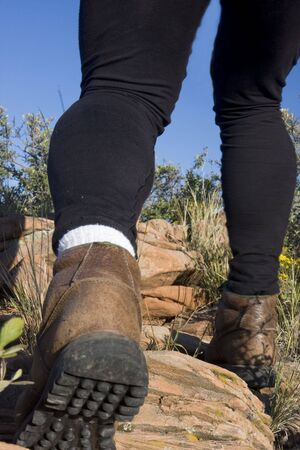 redstone: hiker legs with heavy leather shoes and black tights on a moutain uphill trail Stock Photo