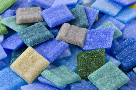 dominant color: a pile of frosty glass small square mosaic tiles with  blue and green dominant color