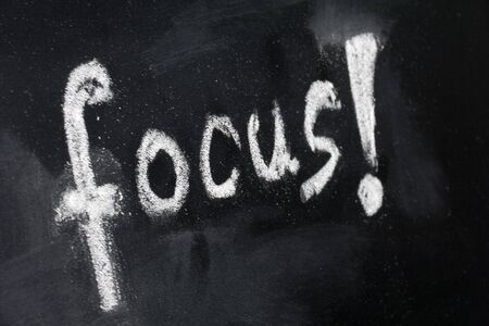 word focus with exclamation mark handwritten with white chalk on a blackboard