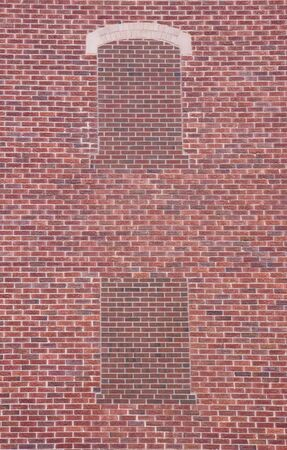 large brick wall of 1924 building with two bliind windows bricked up recently - texture difference between old and modern material Stock Photo