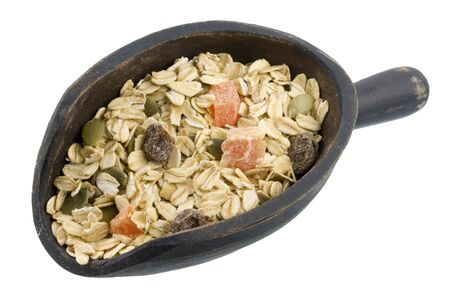 muesli cereal with papaya fruit, pepitas and raisins on a primitive, wooden scoop Stock Photo - 3636063