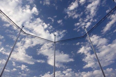 lancer marteau: une vue du ciel bleu avec des nuages blancs � travers un filet de cage de protection pour marteau ou d'une bille jeter la concurrence - Notion de libert�