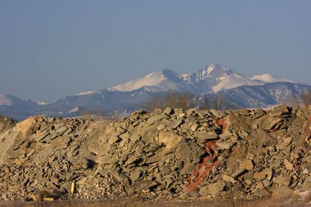 piles of concrete and construction waste obscure a view to snowy peaks of Rocky Mountains (Longs Peak in Colorado)