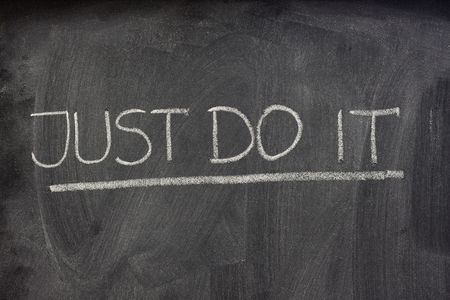 Motivational phrase, just do it, hadwritten with white chalk on a blackboard Stock Photo
