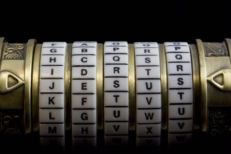 word set up as a password to combination puzzle box (cryptex) with rings of letters, black background Stok Fotoğraf