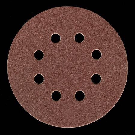 all purpose, fine grit, adhesive backed sanding disk with venting holes on black background Stock Photo