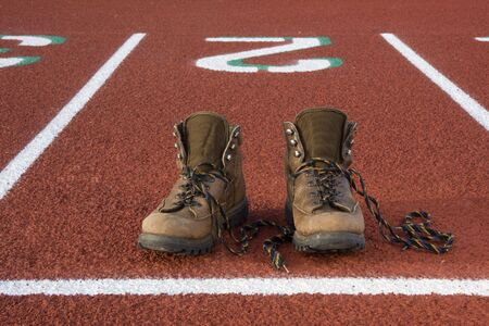 unfit: heavy hiking boots at starting line on a running track, concept - wrong equipment for a job
