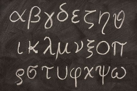 twenty four letters of Greek alphabet from alpha to omega  (in lower case) handwritten with white chalk on a blackboard Stock Photo