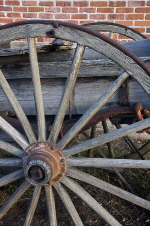 detail of an old wagon with wooden wheels againts brick wall Stock Photo - 3755583