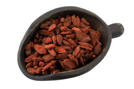 wildberry: dried Tibetan goji berries (wolfberries) on a primitive, wooden, dark painted scoop, isolated on white