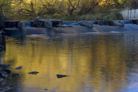 cache la poudre: One of the diversion dams on Cache la Poudre River  in Colorado near Fort Collins supplying water for farmland irrigation, fall scenery with gold foliage and low flow. Stock Photo
