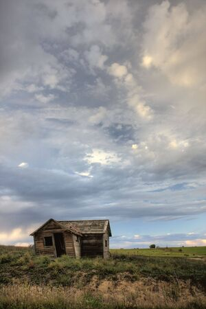 old abandoned farm house on Colorado prairie with green harvested alfalfa fields in background and stormy sky Stock Photo - 3800616