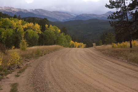 dirt road in Rocky Mountains, Colorado, with aspen tree turning gold and peaks disappearing in clouds Stock Photo - 3815556