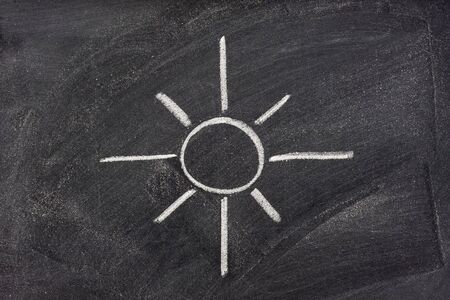 brightness: modern western symbol for sun, sunshine, and light in general, also brightness control on houshold appliances, sketched with white chalk on blackboard