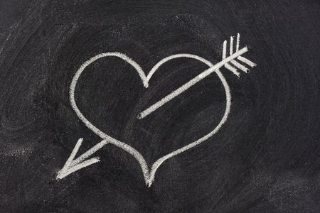 eraser mark: heart pierced by arrow, a modern symbol of sexual love, sketched with white chalk on blackboard