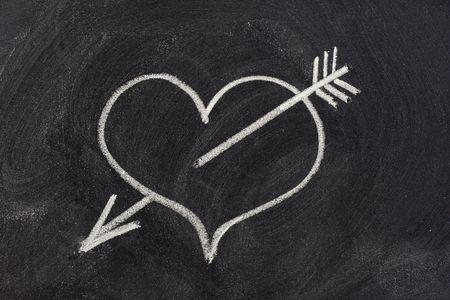 durchbohrt: Herz durchbohrt von Pfeil, ein modernes Symbol der sexuellen Liebe, skizziert mit wei�er Kreide auf Tafel