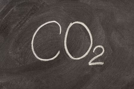 chemical symbol for carbon dioxide, a major greenhouse gas, handwritten with white chalk on a school blackboard Stock Photo