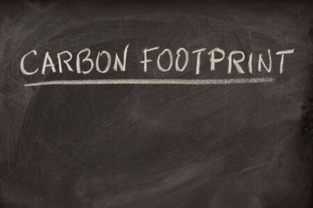 carbon footprint: carbon footprint as lecture title or class topic handwritten with white chalk on a school blackboard