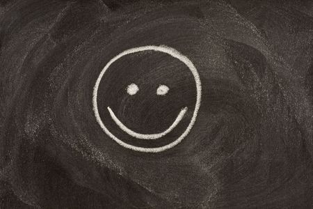 smile sign (smiley) sketched with white chalk on blackboard