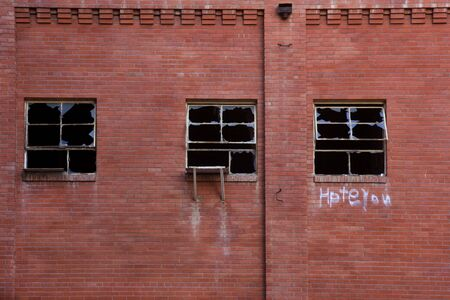 abandoned factory: brick wall of old abandoned factory building with three broken windows and hate you graffiti Stock Photo