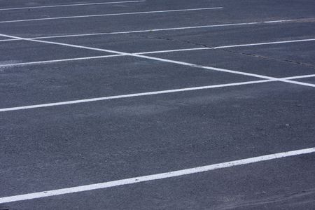 empty parking lot with rough, cracked asphalt pavement and white lines