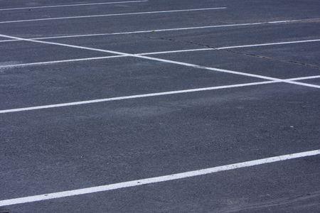 lege parkeer terrein met ruwe, gebarsten asfalt pavement en witte lijnen