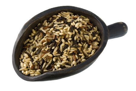 colorful blend of several varieties of whole grain brown and wild rice on a rustic, wooden scoop, isolated on white Stock Photo - 3865328