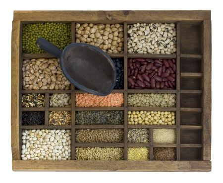 vintage scoop and old, wooden typesetter case with assorted beans, lentils, grains and seeds isolated with clipping path