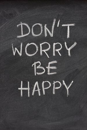 dont worry: dont worry be happy phrase, a quote from Meher Baba, an Indian mystic and spiritual master (before it was used in a song lyrics), hadwritten with white chalk on  on blackboard
