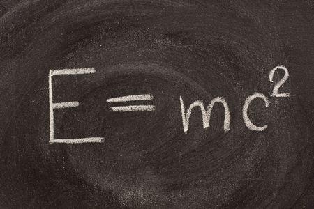 matter: Albert Einstein bekende fysieke formule E = mc2, een beschrijving van de gelijkwaardigheid van de materie massa (m) en energie (E), met inbegrip van de snelheid van het licht. Het is hadwritten met wit krijt op school bord met sterke vlekken patronen.