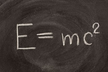 describing: Albert Einstein well known physical formula, E=mc2, describing equivalence of matter mass (m) and energy (E) with including speed of light.  It is hadwritten with white chalk on school blackboard with strong smudge patterns. Stock Photo