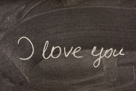 smudge: I love you handwritten with white chalk on school blackboard with strong smudge patterns from eraser