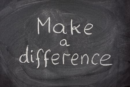 phrase: make a difference motivational phrase handwritten with white chalk on blackboard Stock Photo