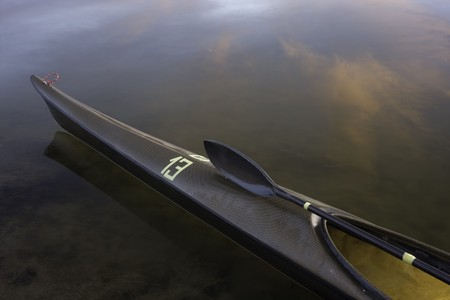 kevlar: bow of sea racing kayak (lightweight and slim carbon kevlar fiber design) with a wing paddle across cockpit on calm water with cloud reflections, temporary racing number 13 on front deck, wet after paddling  l  eightweight carbon kevlar racing sea kayak w Stock Photo