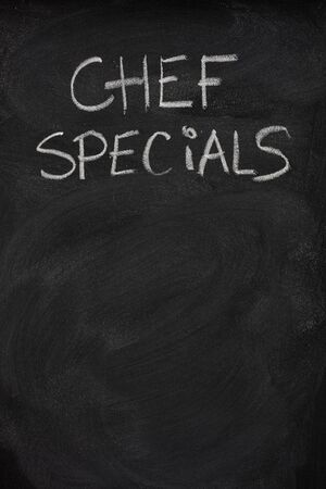 chef specials title handwritten with white chalk on blackboard, copy space below photo