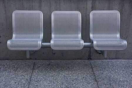 three modern perforated metal chairs against a concrete wall