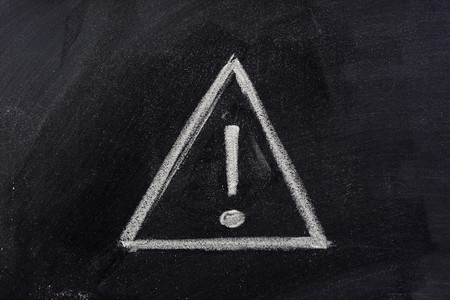 warning sign, exclamation mark inside a triangle, sketched with white chalk on blackboard Stockfoto