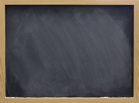 blank blackboard in wooden frame with white chalk dust and eraser smudges photo