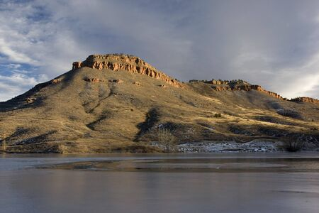 Flatiron Reservoir covered partially by ice surrounded by hills and sandstone cliffs in foothils of Rocky Mountains in Colorado near Loveland Stock Photo - 4067783