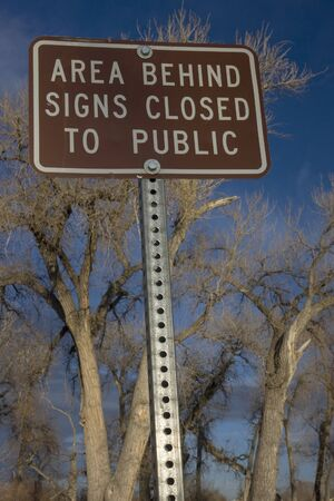 area behind signs closed to public - metal brown sign with cottonwood trees in background Imagens