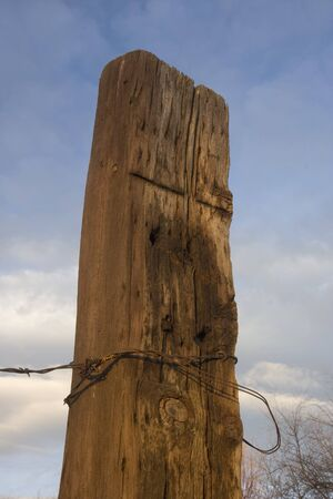 solid wooden fence post (railroad tie)  with a barbed wire attached against blue sky and clouds Stock Photo - 4082103