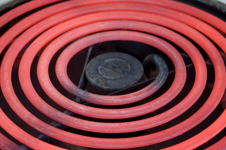 oven and range: close-up of red glowing heating element of electric range oven, selective focus