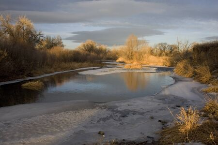 cache la poudre: small river, Cache la Poudre below Fort Collins, Colorado, partially frozen with low flow on winter sunset Stock Photo